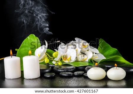 beautiful spa concept of blooming white orchid flower, phalaenopsis, green leaf with dew, smoke stick and candles on black zen stones, close up - stock photo
