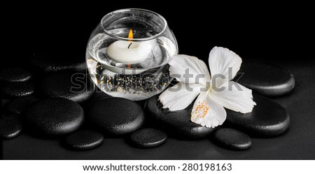 beautiful spa concept of dew white hibiscus flower and candles in vase with water on zen stones, panorama  - stock photo