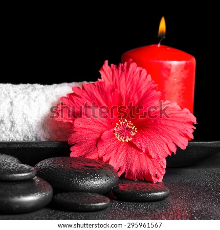 beautiful spa concept of hibiscus flower with dew, red candles and white rolled towel tied with ribbon on zen stones, closeup - stock photo