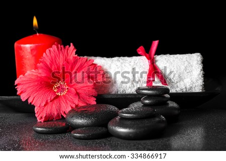 beautiful spa concept of hibiscus flower with dew, red candles and white rolled towel tied with ribbon on zen stones - stock photo