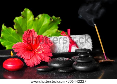 beautiful spa concept of red hibiscus flower with dew, candles, green leaf, scent stick and rolled towel on zen stones - stock photo