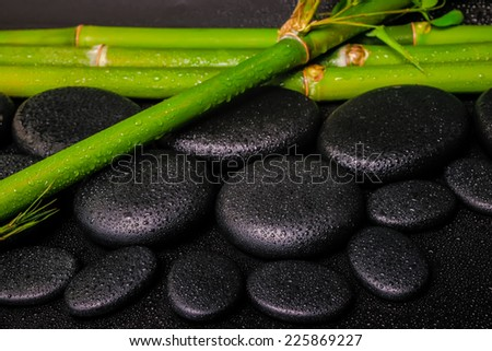 beautiful spa setting of zen basalt stones and natural bamboo stems with dew, closeup - stock photo
