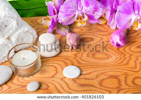 beautiful spa setting with blooming lilac orchid, white stones, towels, candle and big green leaf on root wood background, close up  - stock photo