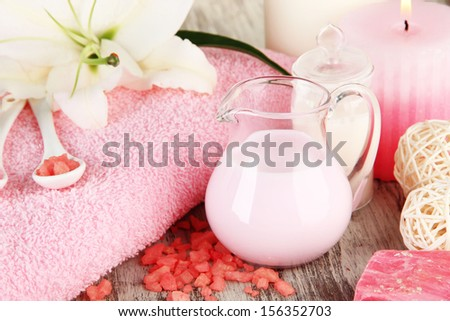 Beautiful spa setting with lily on wooden table close-up - stock photo