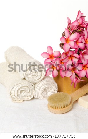 Beautiful spa setting with towel with soap, branch frangipani - stock photo