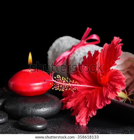 beautiful spa still life of red hibiscus flower with dew, candles and white rolled towel on zen stones, close up - stock photo