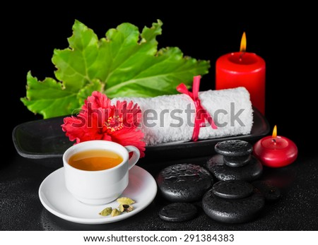 beautiful spa still life of red hibiscus flower with dew, candles, green leaf, cup of tea and rolled towel on zen stones - stock photo