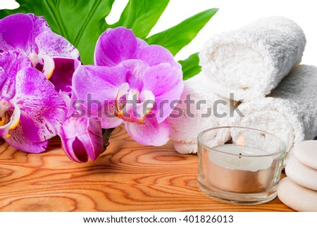 beautiful spa still life with blooming lilac orchid, white stones, towels, candle and tropical green leaf on root wood background is isolated, close up  - stock photo