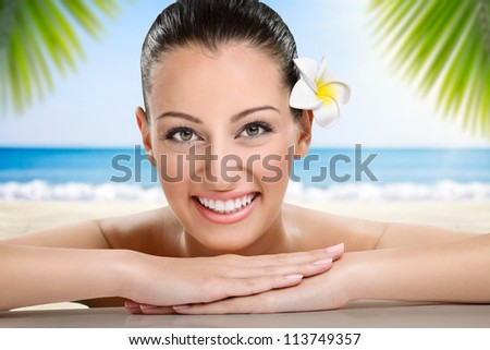Beautiful spa woman smiling, health and beauty, against the beach - stock photo