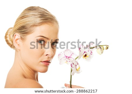 Beautiful spa woman with an orchid flower. - stock photo