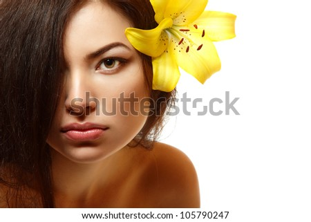 beautiful spa young multiracial woman with yellow flower lily in her hair. Isolated on white background - stock photo