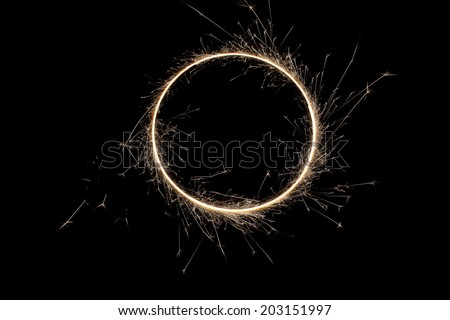 Beautiful sparkle sparklers in a circle on a black background. High resolution. - stock photo
