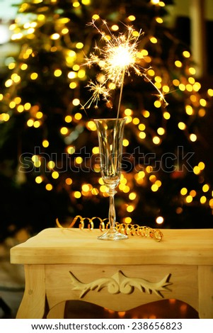 Beautiful sparkler in glass on shiny background, close up - stock photo