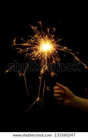 beautiful sparkler in woman hand on black background - stock photo