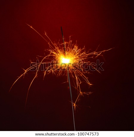 beautiful sparkler on red background - stock photo