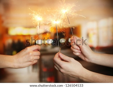 beautiful sparklers in woman hands on room background - stock photo