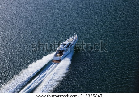 Beautiful speed boat sailing through the sea on a bright sunny day - stock photo