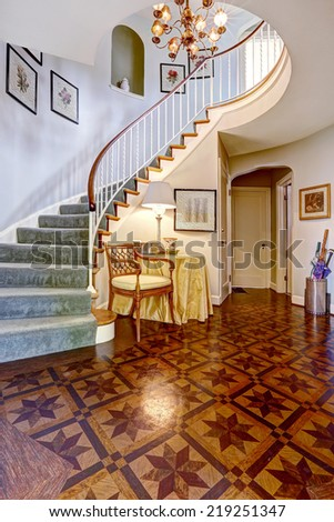Beautiful spiral staircase with railings and carpet steps in luxury foyer with high ceiling and designed hardwood floor - stock photo