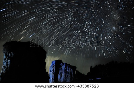 Beautiful spiral star trails over rock. Beautiful night sky. - stock photo