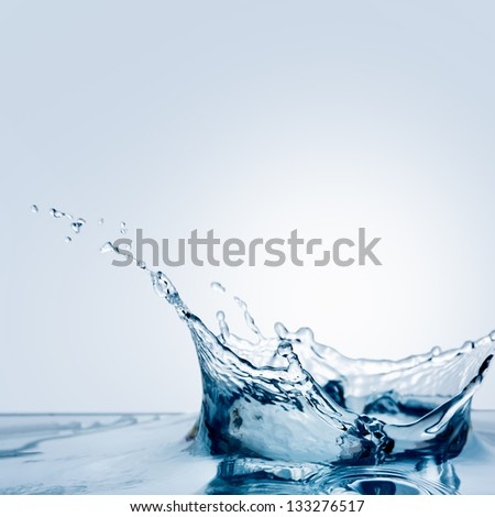 Beautiful splash of water falling from a slice of lemon - stock photo