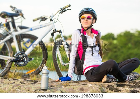 Beautiful sport smiling girl sitting next to bike, summer time - stock photo