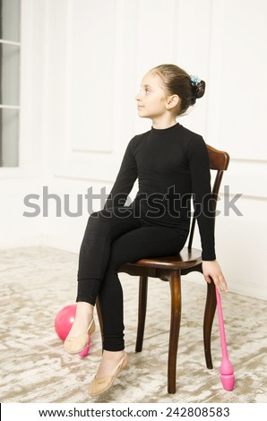 beautiful sport training rhythmic gymnastic girl with Rhythmic pink clubs doing professional exercises in white training room. sitting on wooden chair  - stock photo