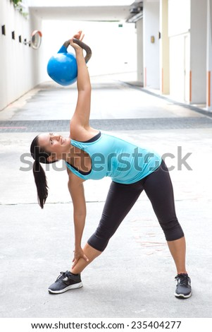 Beautiful sport woman in blue with blue dumb bell demonstrating the windmill pose  - stock photo