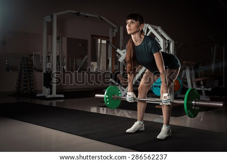 beautiful sports fitness girl with a barbell in the gym - stock photo