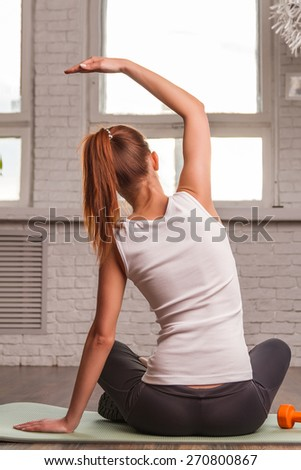 Beautiful sports girl does exercises sitting back on the mat. soft light - stock photo