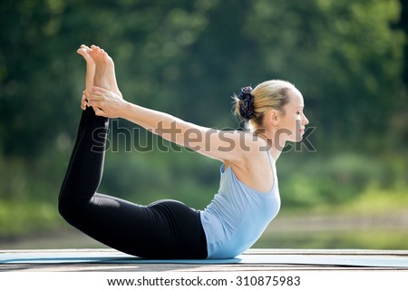 Beautiful sporty fit blond young woman wearing blue tank top sportswear working out outdoors on summer day, doing basic posture Dhanurasana, Bow Pose, full length - stock photo