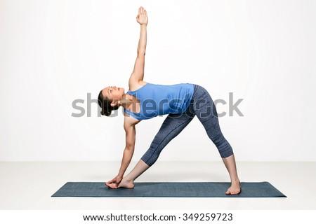 Beautiful sporty fit woman practices Ashtanga Vinyasa yoga asana utthita trikonasana - extended triangle pose - stock photo