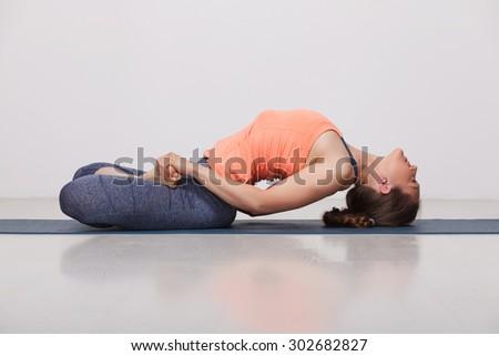 Beautiful sporty fit yogini woman practices yoga asana Matsyasana - fish pose in studio - stock photo