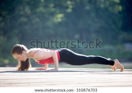 Beautiful sporty fit young woman in sportswear working out outdoors on summer day, doing push-ups, chaturanga dandasana, four-limbed staff posture, exercises for shoulders and abs muscles - stock photo