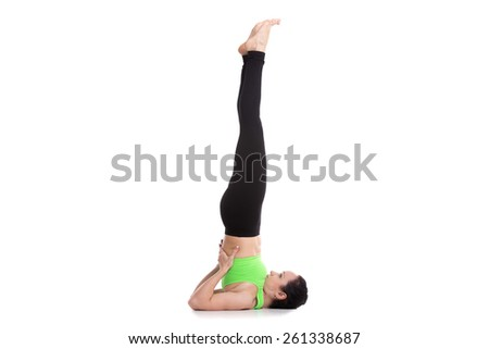 Beautiful sporty girl doing yoga exercises for abs strength, Supported Shoulderstand asana, Salamba Sarvangasana - stock photo