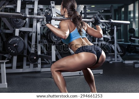 beautiful sporty sexy woman doing squat workout in gym - stock photo