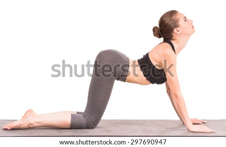 Beautiful sporty woman doing yoga exercise in cat position and looking up. - stock photo