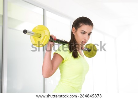 Beautiful sporty woman hold barbell on shoulder? in gym - stock photo