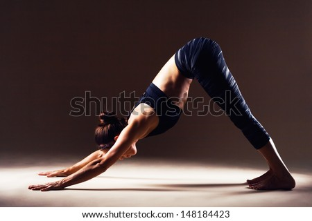 Beautiful sporty woman is working out. Downward-facing dog. Adho Mukha Svanasana. - stock photo