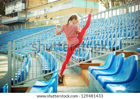 Beautiful sporty woman is working out on stadium - stock photo