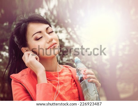 Beautiful sporty woman listening music on headphones - stock photo