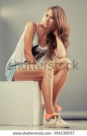 Beautiful sporty woman sitting on a big white cube - stock photo