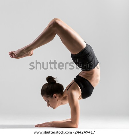 Beautiful sporty yogi girl practices yoga asana, Scorpion Pose Vrischikasana, forearm stand, inverted backbend pose - stock photo