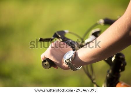 Beautiful sporty young woman hand griping bicycle handle in bright sunlight on summer day, close up - stock photo