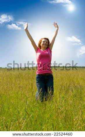beautiful spreading her arms in the middle of a field - stock photo