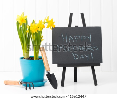 Beautiful spring daffodils and a Mothers Day message on a slate. - stock photo