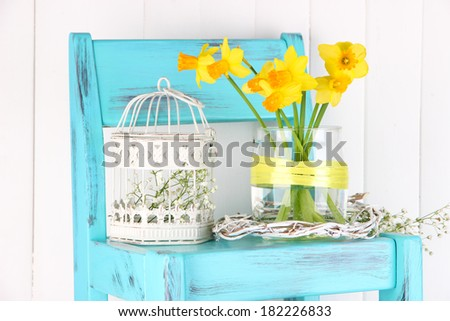 Beautiful spring flowers on blue old wooden chair  - stock photo