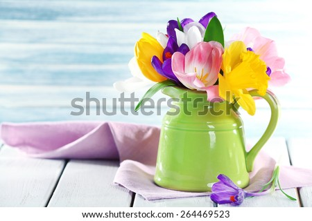 Beautiful spring flowers on wooden table on blue background - stock photo