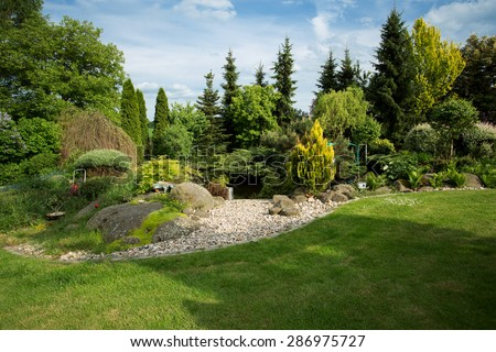 Beautiful spring garden design, with conifer trees, green grass and pond - stock photo