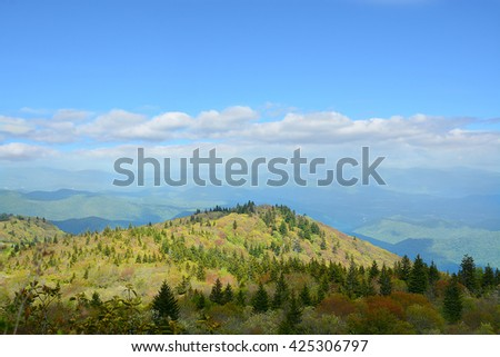 Beautiful spring mountain landscape. Colorful blooming trees and blue sky with white clouds in the background. Copy space. North Carolina. Blue Ridge Mountains. USA - stock photo