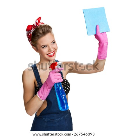 Beautiful staff wearing pink rubber protective gloves holding cleaning spray bottle and cellulose sponge / young beautiful American pin-up girl isolated on white background. Cleaning service concept - stock photo